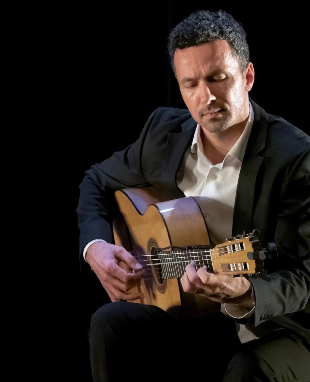 Dan MacNeil seated Playing flamenco guitar