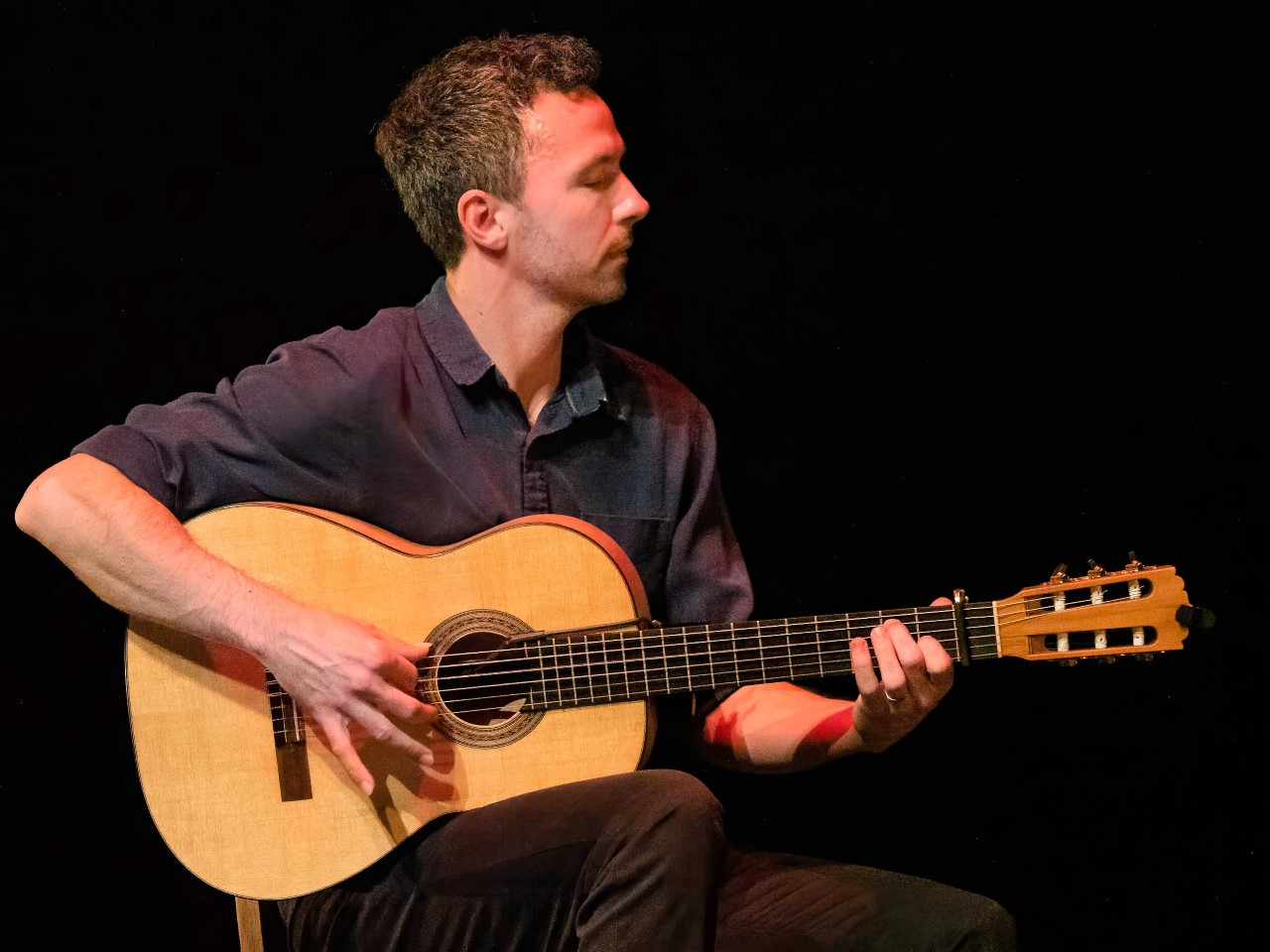 dan macneil playing flamenco guitar on stage
