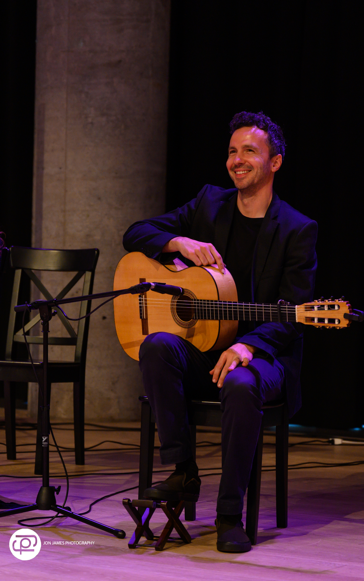 Dan Macneil on stage holding flamenco guitar and smiling at audience