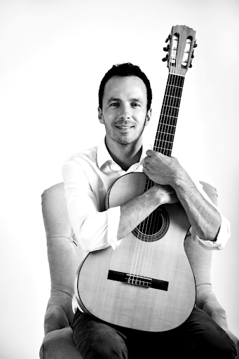 Daniel Macneil seated holding Flamenco guitar