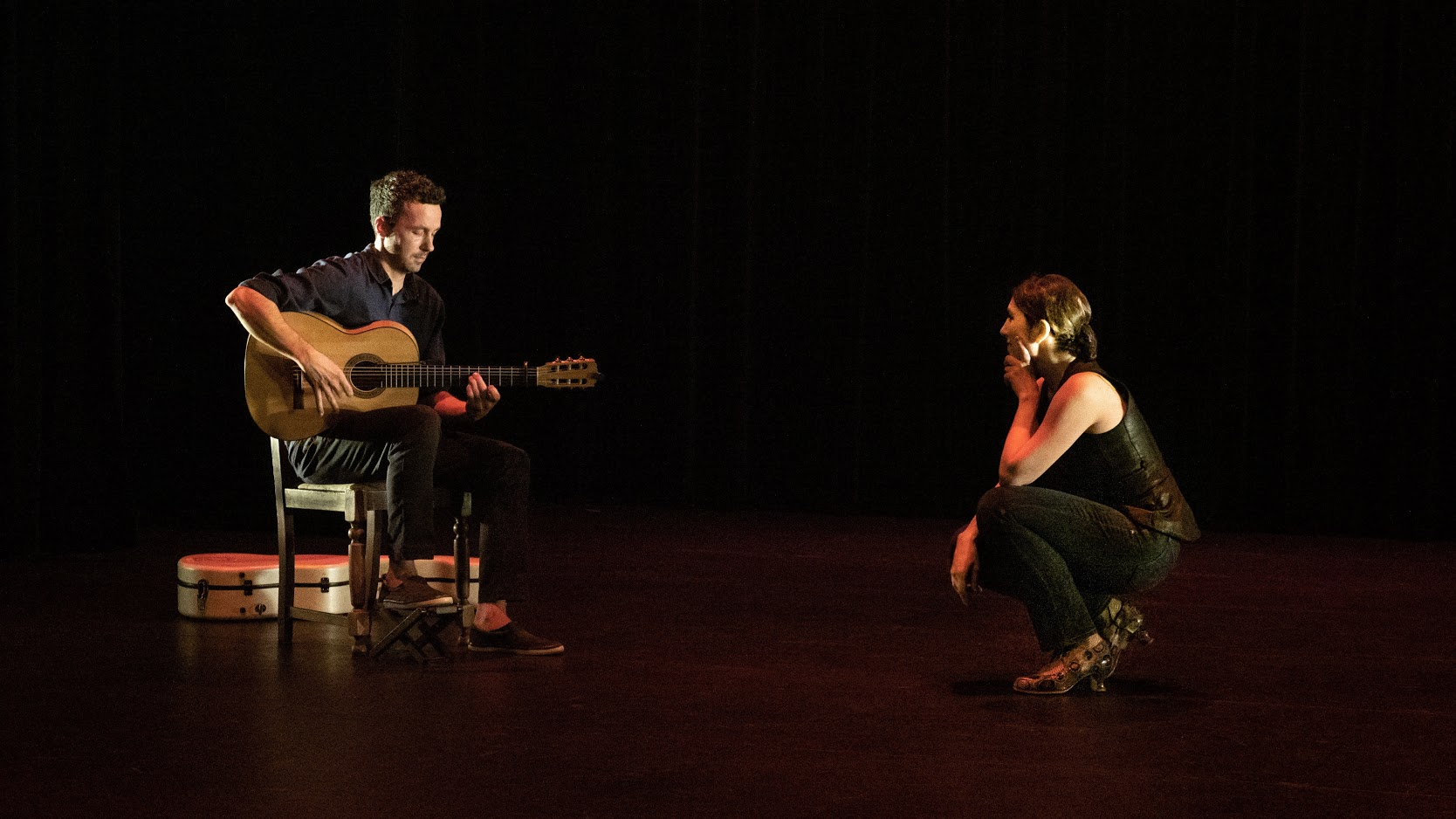 Dancer Maria Osende crouches down on stage and watches dan macneil play flamenco guitar