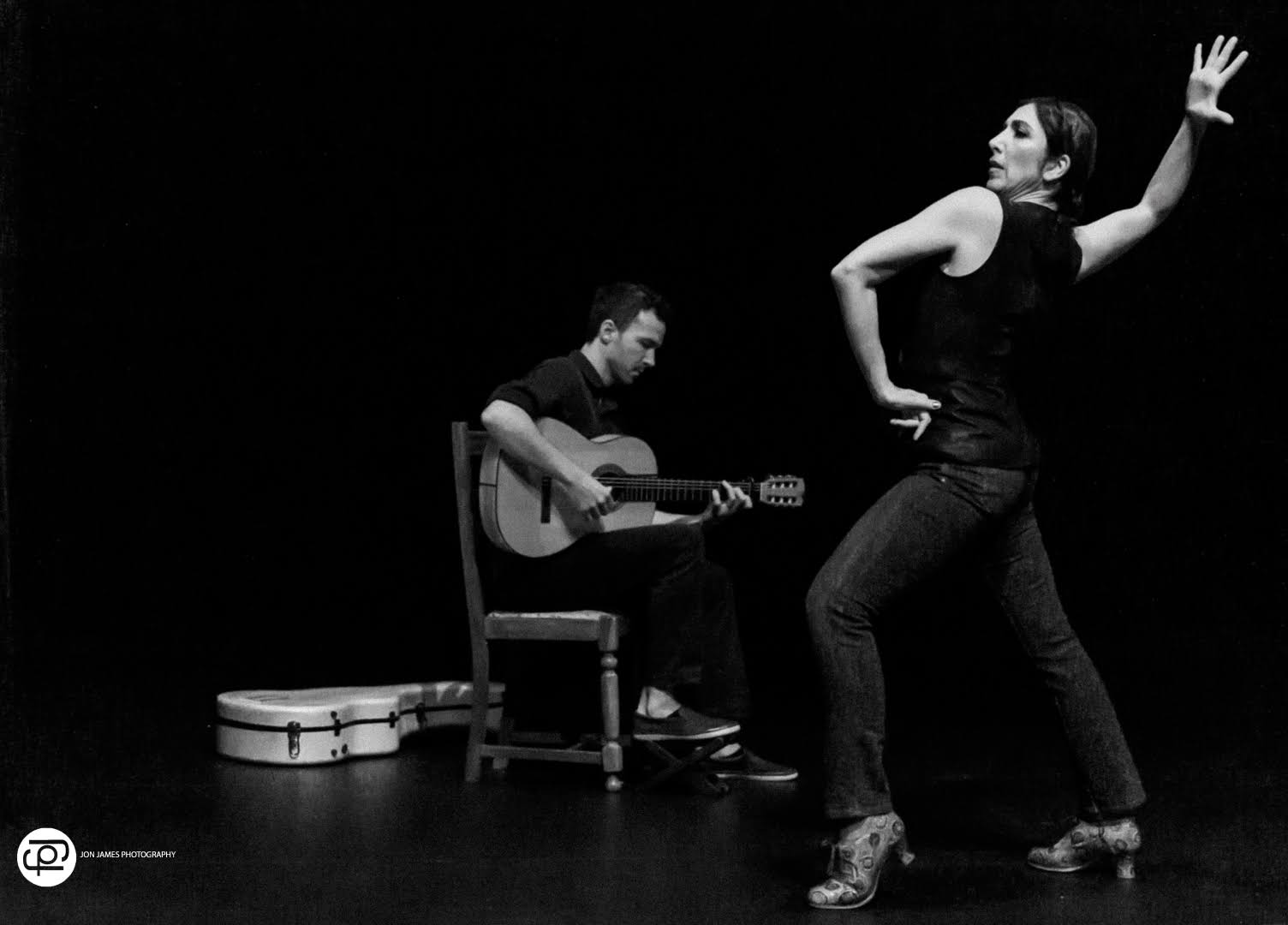 dan macneil seated in background playing flamenco guitar while maria osende strikes a powerful dance pose