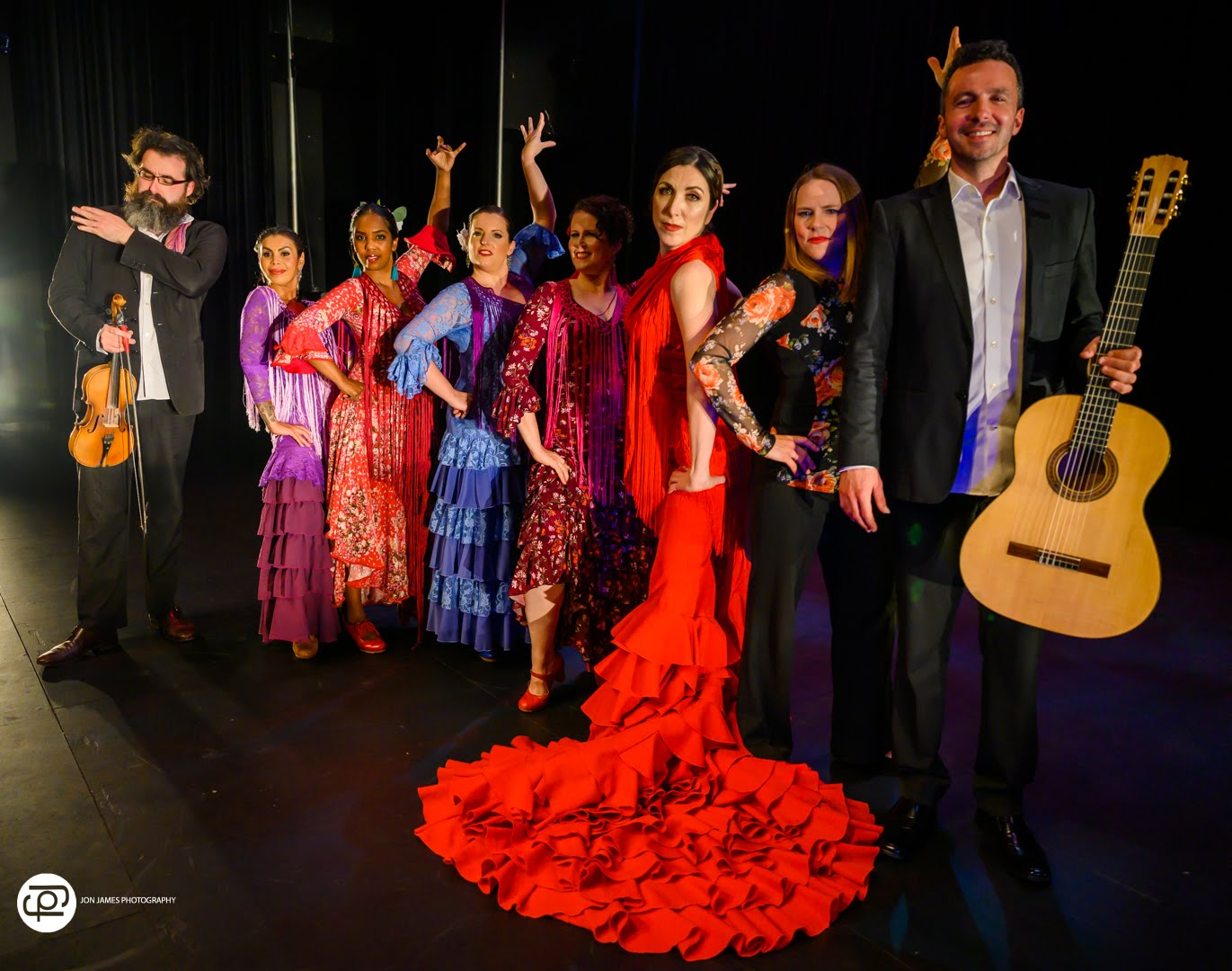 dan macneil stands with guitar and front of long line of brightly costumed dancers and musicians