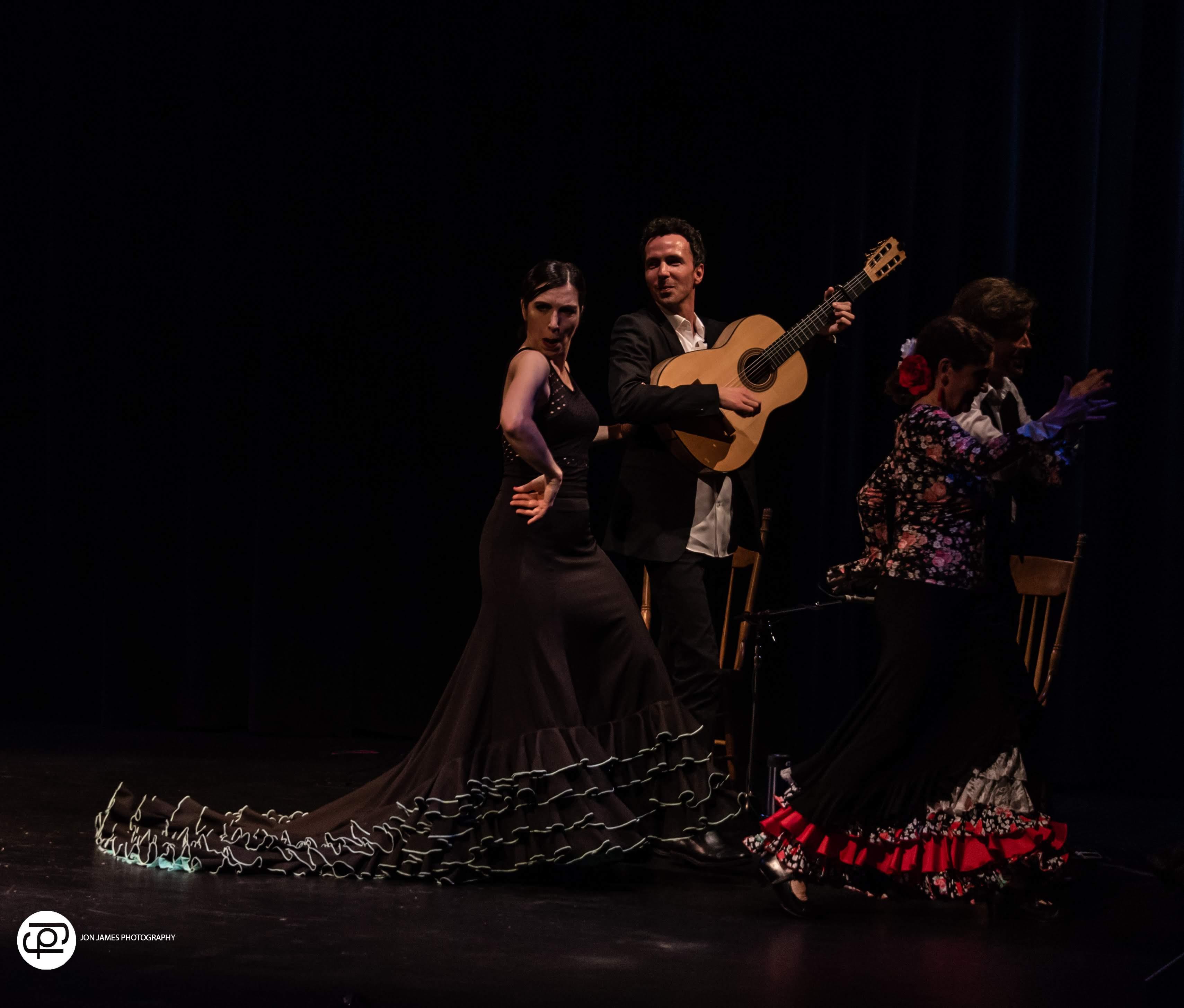 dan macneil and maria osende walk playfully offstage while dan plays flamenco guitar